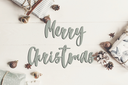 merry christmas text, seasonal greetings card sign. flat lay. presents with ornaments and pine cones anise on white wooden background top view, Stock Photo