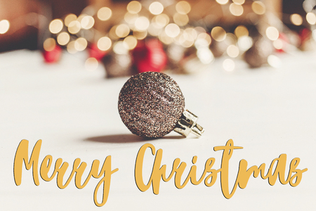 merry christmas text, seasonal greetings card sign. glitter christmas ornament with illumination lights on white wooden background. merry xmas
