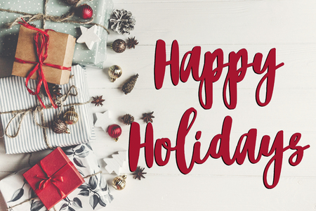 happy holidays text, seasonal greetings card sign. flat lay. presents with ornaments pine cones anise  on rustic white wooden background top view