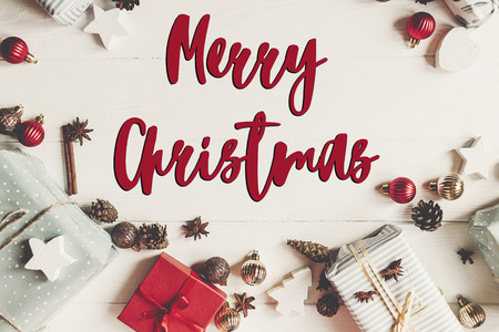 merry christmas text, seasonal greetings card sign. wrapped present boxes with ornaments with cones anise on white wooden background top view,  flat lay.