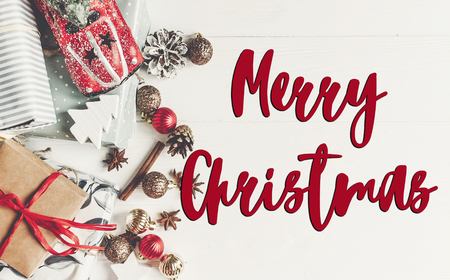 merry christmas text, seasonal greetings card sign.  flat lay. wrapped presents with ornaments  car toy and pine cones anise on rustic white wooden background top view, Stock Photo