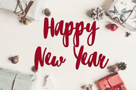 happy new year text, seasonal greetings card sign. stylish wrapped present boxes with ornaments on white wooden background top view, christmas flat lay.