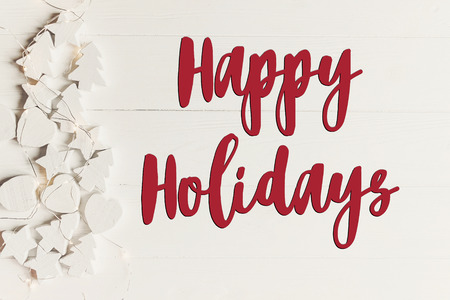 happy holidays text, seasonal greetings card sign. minimalistic christmas flat lay. simple wooden white christmas ornaments trees and stars frame or border with lights, top view