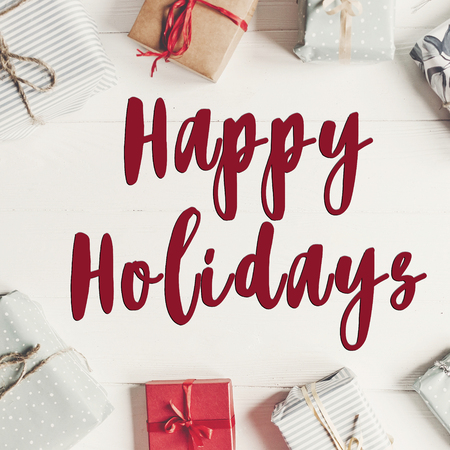 happy holidays text, seasonal greetings card sign. wrapped present boxes on white wooden background top view, flat lay.