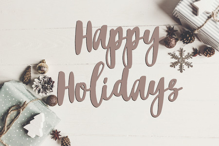 happy holidays text, seasonal greetings card sign. flat lay. stylish presents and gifts with ornaments cones anise on rustic white wood top view