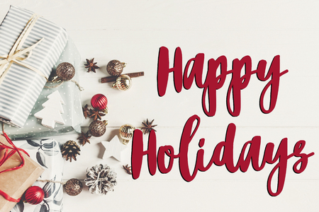 happy holidays text, seasonal greetings card sign. christmas flat lay. wrapped presents with ornaments and pine cones anise on rustic white wooden background top view, stylish gifts.
