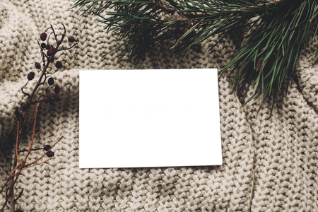christmas card mockup. empty christmas card with space for text, template on knitted sweater and fir branches.  merry christmas, seasonal greetings, happy holidays. atmospheric  moments