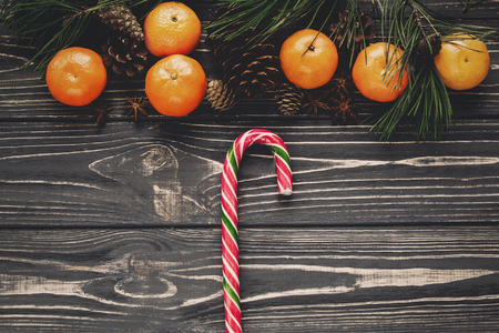 christmas flat lay. candy lollipops canes on rustic wooden background with cones and anise and tangerine, top view. merry christmas, seasonal greetings, happy holidays. space for text Stock Photo