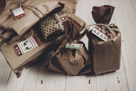verpakte rustieke papieren geschenkdozen. Kerstcadeaus met tag op witte rustieke houten achtergrond. fijne kerstdagen, seizoensgroeten, fijne feestdagen. atmosferische hygiënische momenten