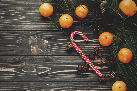 fresh tangerines and peppermint candy cane with green fir branches with cones on rustic wooden background top view with space for text. winter flat lay image, christmas concept Stock Photo