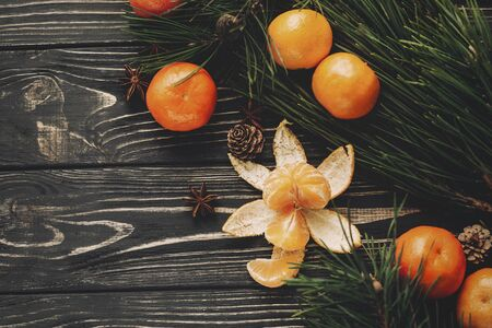 christmas tree branches and peeled tangerine and pine cones anise top view on rustic wooden background, space for text. stylish christmas flat lay, seasonal greetings, happy holidays