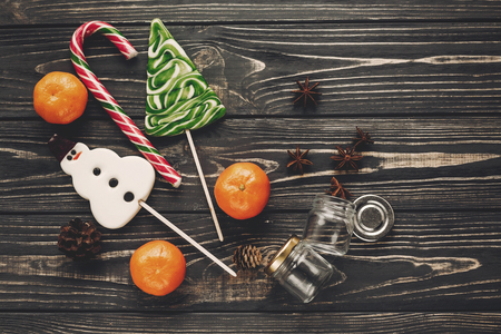 christmas flat lay. sweet candy lollipops canes on rustic wooden background with cones and anise, top view. merry christmas, seasonal greetings, happy holidays. atmospheric  moments Stock Photo