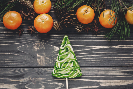 christmas tree candy and tangerines with green fir branches with cones and anise on rustic wooden background top view with space for text. winter flat lay image, christmas concept