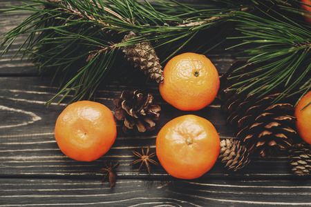 tangerines with green fir branches with cones and anise on rustic wooden background top view with space for text. winter flat lay image, christmas concept
