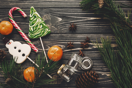 christmas candy and tangerines with green fir branches with cones and anise on rustic wooden background top view with space for text. winter flat lay image, christmas concept Stock Photo