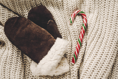 Élégant plat de Noël. gants et canne à sucre de menthe poivrée sur la vue de dessus de fond chandail tricoté rustique, espace pour le texte.