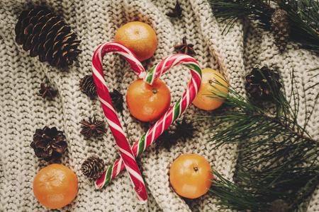 Élégant plat de Noël. canne de bonbon à la menthe poivrée avec des pommes de pin de mandarine anis et branches de sapin sur fond de chandail tricoté rustique vue de dessus.