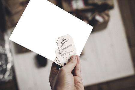 Main tenant l'espace de la carte de Noël pour le texte, sur bois rustique blanc