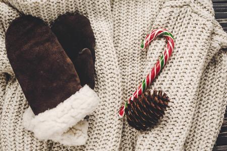 Gants élégants et chandail tricoté avec canne à sucre menthe poivrée et cônes sur fond rustique.