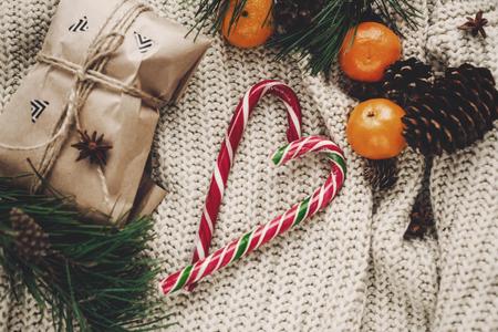 Élégant Noël plat poser artisanat cadeau et canne à sucre de menthe poivrée dans le cœur et les pommes de pin branches de sapin anis avec mandarine sur pull tricoté rustique Banque d'images