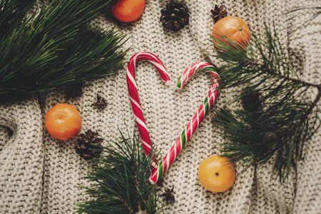 Canne en bonbon élégant de menthe poivrée dans le coeur et les cônes de pin mandarine et anis avec des branches de sapin sur le chandail tricoté rustique vue de dessus Banque d'images