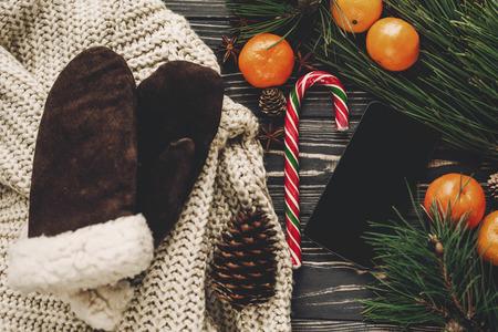 Élégant plat de Noël. gants chandail tricoté et téléphone intelligent et branches de sapin avec des cônes de mandarine candy et anis sur vue de dessus de fond en bois rustique.