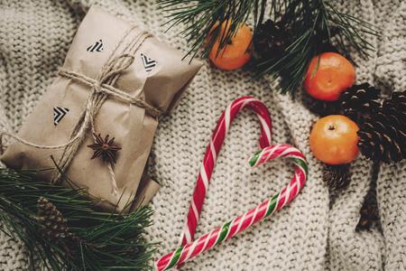 Artisanat élégant cadeau et canne à sucre de menthe poivrée en cœur et pommes de pin sapin branches anis avec mandarine sur pull en tricot rustique vue de dessus Banque d'images