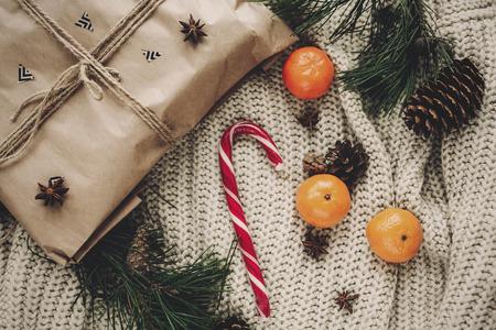 Élégant Noël plat poser artisanat cadeau et de la canne à sucre de menthe poivrée et de cônes de pin branches de sapin anis avec mandarine sur chandail tricoté rustique vue de dessus Banque d'images