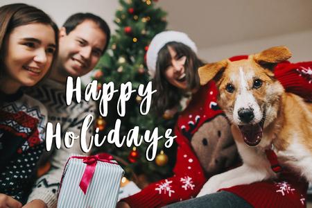 signe de texte de joyeuses fêtes, carte de voeux. famille heureuse s'amuser avec un cadeau et un chien drôle à l'arbre de Noël. moments émotionnels, salutations saisonnières. fête. atmosphérique