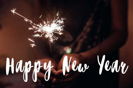 happy new year text sign, greeting card.hand holding a burning sparkler firework bengal light. burning sparkler closeup in female hand in dark. happy new year. happy holidays
