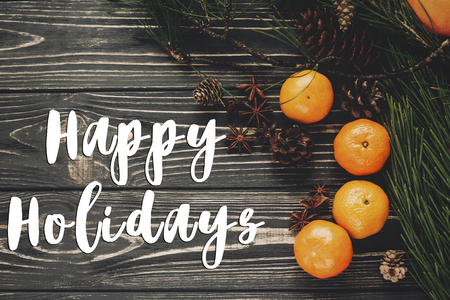 happy holidays text sign, greeting card. tangerines with green fir branches with cones and anise on rustic wooden background top view. winter flat lay image, christmas concept