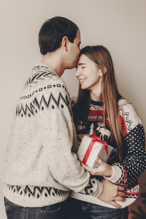 merry christmas and happy new year concept. stylish hipster couple in sweaters holding gift with red bow in room at christmas tree with lights and kissing. happy holidays. family  moments Stock Photo