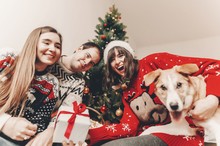 happy family in stylish sweaters and cute funny dog exchanging gifts at christmas tree with lights. emotional moments. merry christmas and happy new year concept. space for text
