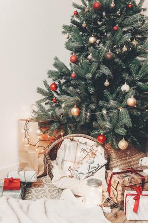 bel arbre de Noël traditionnel avec des lumières, un espace pour le texte. cadeaux et cadeaux sous l'arbre avec des ornements dans la salle de fête. joyeuses fêtes. Joyeux Noël et bonne année concept