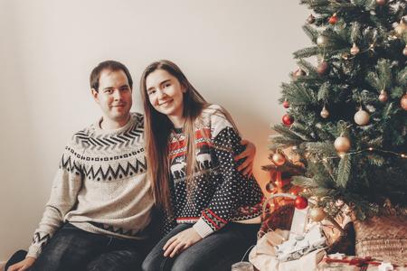 couple élégant dans des chandails, étreindre et souriant à l'arbre de Noël dans la salle de soirée confortable. moments atmosphériques. joyeux Noël et bonne année concept. joyeuses fêtes