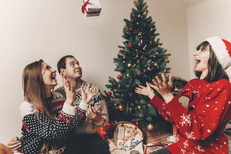 joyeux Noël et bonne année concept. famille de hipster élégant dans des chandails festifs jetant des cadeaux aux lumières d'arbre de Noël. joyeuses fêtes. moments émotionnels drôles Banque d'images