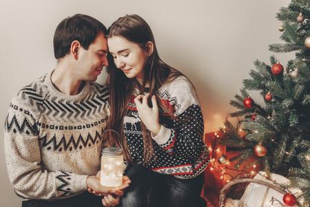 couple heureux dans des chandails élégants tenant la lumière de la lanterne dans la salle de fête à l'arbre de Noël et embrassant. moments festifs atmosphériques. Joyeux Noël et bonne année concept Banque d'images