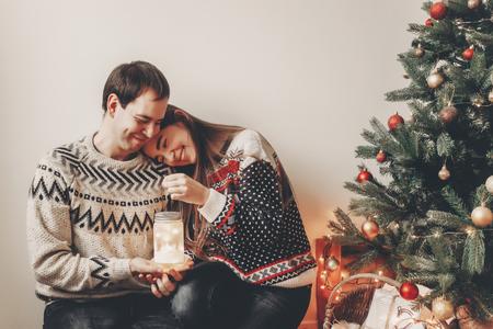 couple heureux dans des chandails élégants tenant la lumière de la lanterne dans la salle de fête à l'arbre de Noël et souriant. moments festifs atmosphériques. Joyeux Noël et bonne année concept