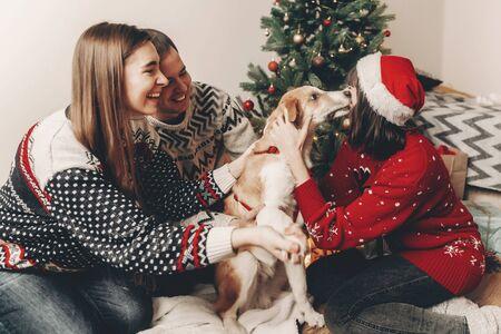 joyeux Noël et bonne année concept. famille élégante de hipster dans les chandails festifs jouant et souriant avec le chien mignon aux lumières d'arbre de Noël. joyeuses fêtes. moments émotionnels atmosphériques