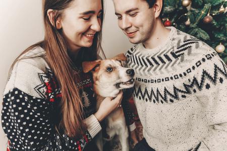 couple élégant hipster dans des pulls jouant avec chien et souriant à l'arbre de Noël dans la salle festive. moments atmosphériques. joyeux Noël et bonne année concept. joyeuses fêtes
