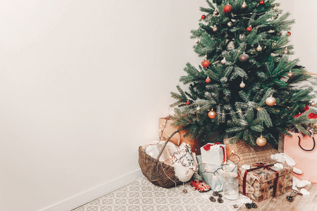 merry christmas and happy new year concept. festive room with christmas tree with lights, space for text. gifts and presents under tree. happy holidays Stock Photo