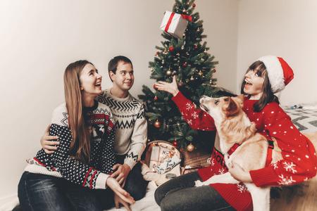 famille heureuse dans des chandails élégants et chien drôle mignon échanger des cadeaux à l'arbre de Noël avec des lumières. moments émotionnels. joyeux Noël et bonne année concept. espace pour le texte Banque d'images