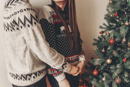couple heureux dans des chandails élégants décoration arbre de Noël et embrassant. joyeux Noël et bonne année concept. espace pour le texte .. moments de famille douillette