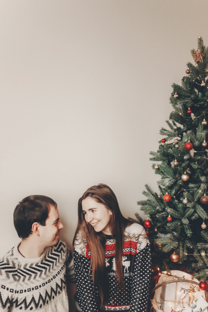 stylish couple in sweaters hugging and smiling at christmas tree in cozy evening room. atmospheric moments. merry christmas and happy new year concept. happy holidays