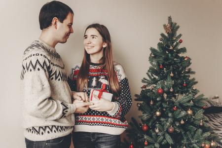 couple heureux dans des chandails élégants échangeant et ouvrant le cadeau avec l'arc dans la salle de fête à l'arbre de Noël. moments festifs atmosphériques. Joyeux Noël et bonne année concept