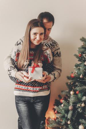 Famille heureuse dans des chandails élégants, échangeant des cadeaux dans la salle festive avec arbre de Noël et des lumières. moments émotionnels. joyeux Noël et bonne année concept. joyeuses fêtes Banque d'images