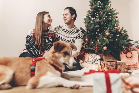 joyeux Noël et bonne année concept. famille heureuse dans des chandails élégants et chien mignon à l'arbre de Noël avec des lumières et des cadeaux. moments festifs atmosphériques. espace pour le texte