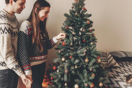 couple heureux dans des chandails élégants décoration arbre de Noël dans la chambre. joyeux Noël et bonne année concept. espace pour le texte. femme mettant des ornements. moments agréables en famille Banque d'images