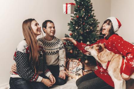 joyeux Noël et bonne année concept. famille hipster élégant dans des chandails festifs avec chien mignon jetant cadeau à des lumières d'arbre de Noël. joyeuses fêtes. moments émotionnels drôles