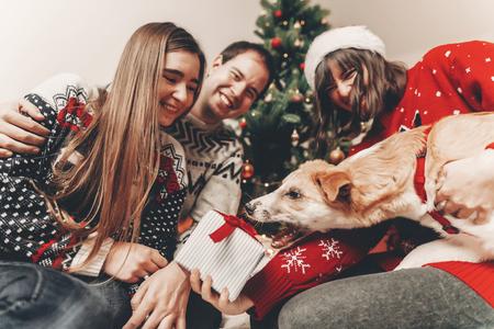 Famille heureuse dans des chandails élégants et chien mignon s'amuser avec des cadeaux à l'arbre de Noël avec des lumières. moments émotionnels atmosphériques. joyeux Noël et bonne année concept. espace pour le texte